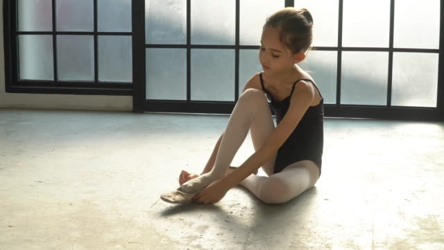 4k wide shot young little child girl ballerina dancer in black leotard for dancing sitting on the floor in studio room wearing and tie ballet slipper shoe for private ballet dance practice. - danza classica video stock e b–roll