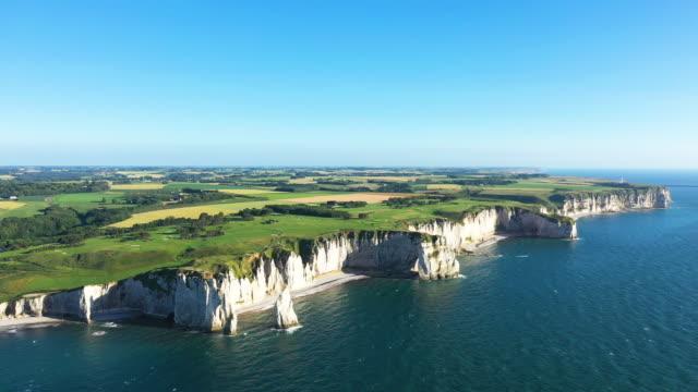 Wide view in straight lateral motion on the cliffs of Etretat on a sunny cloudless day Cette photo a été prise en France, au nord de la Normandie, à Etretat et avec un drone. Il s'agit d'une vue globale sur les falaises, les plages et les champs en arrière plan. normandy stock videos & royalty-free footage