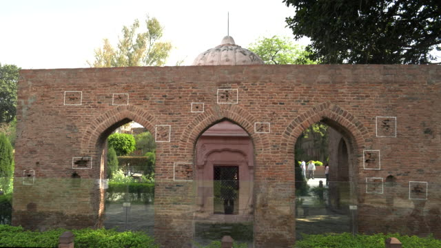 wide view of a bullet marked wall at jallianwala bagh