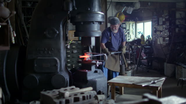 Wide view of blacksmith in workshop using industrial hammer video