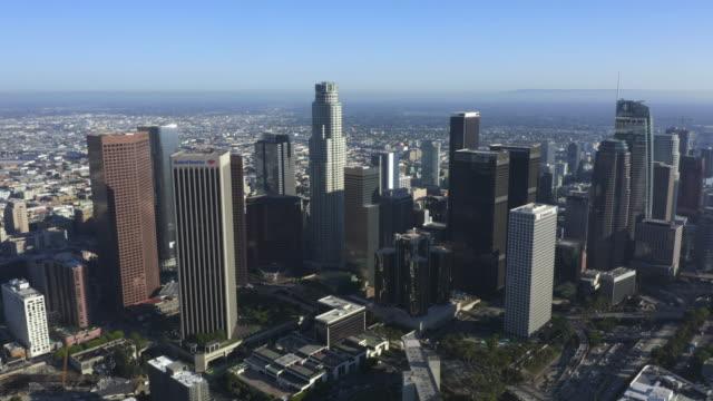 aerial: güzel mavi gökyüzü ve güneşli bir günde downtown los angeles, california skyline geniş görünümü [4k] - los angeles stok videoları ve detay görüntü çekimi