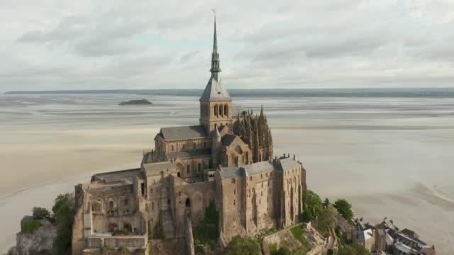 vídeos de stock, filmes e b-roll de ampla vista do castelo le mont saint michel no oceano na frança, aéreo, nublado - castelo