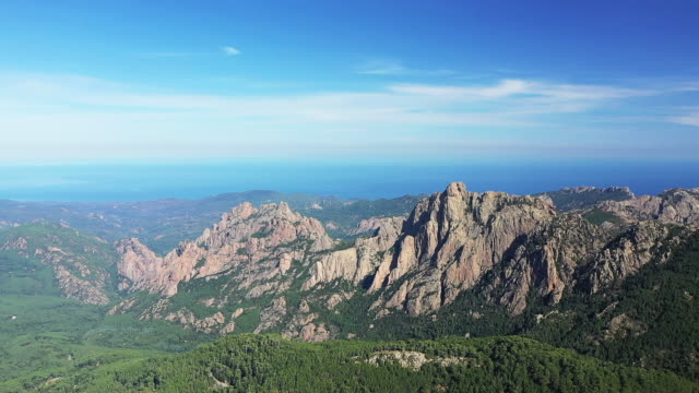 Wide view of the granite rocks and forests of the Bavella Pass on the shores of the Mediterranean Sea in Corsica, France, in summer, by drone.