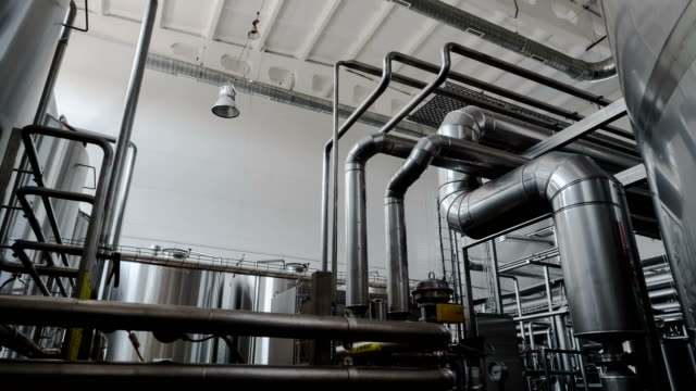 Wide zoom-in shot of industrial interior. Robotic factory line for processing and quality control of pure spring water bottled into canisters. video