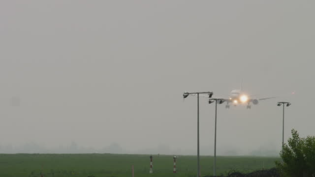 großraumflugzeug landet bei regenwetter - editorial videos stock-videos und b-roll-filmmaterial