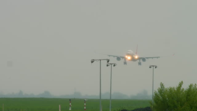 Widebody airplane landing at rainy weather Widebody airplane approaching before landing on runway at rainy weather. Airport of Almaty, Kazakhstan kazakhstan stock videos & royalty-free footage