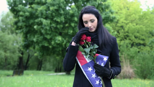 widow of fallen soldier holding americain flag at cemetery - memorial day стоковые видео и кадры b-roll