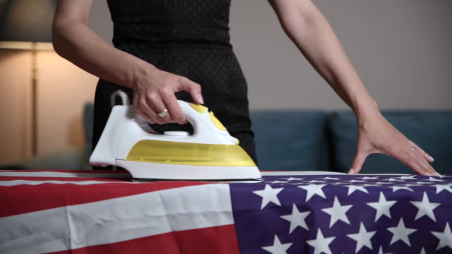 widow of fallen soldier ironing americain flag - memorial day стоковые видео и кадры b-roll