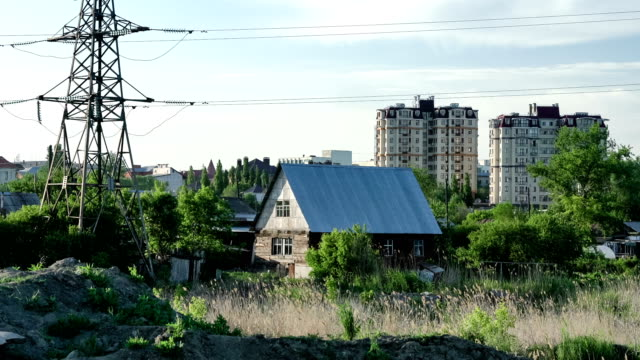 Widw shot of town approaches with old wooden house next to the high-rise apartment houses. video