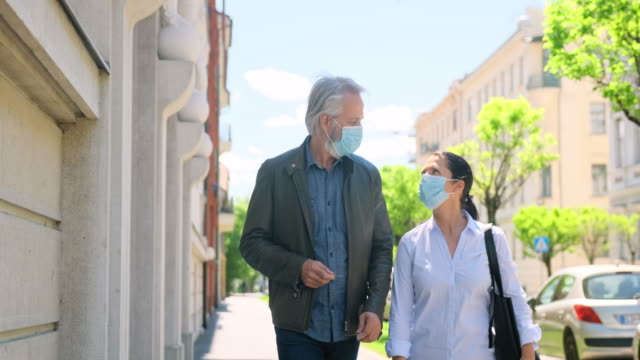 Wife and a Husband in Protective Masks Walking Outdoors video