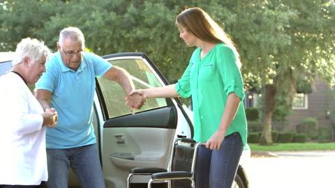 moglie e figlia aiutano l'uomo anziano dall'auto alla sedia a rotelle - accudire video stock e b–roll