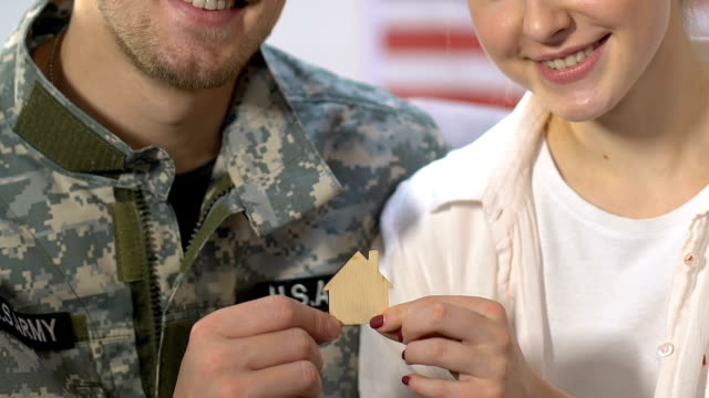 Wife and husband military uniform holding wooden house sign, ownership, mortgage Wife and husband military uniform holding wooden house sign, ownership, mortgage military uniform stock videos & royalty-free footage
