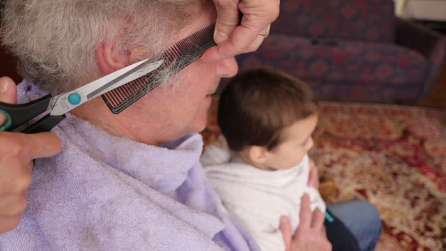 Wife cutting her husband's hair at home Mature, gray haired man sitting at chair and holding his grandson while his wife cutting his hair at living room during covid-19 lockdown wearing a towel stock videos & royalty-free footage