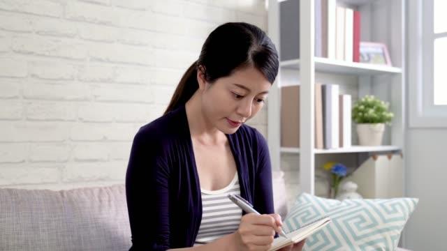 ehefrau sieht sich vor kamera lächelnd, während sie in büchern aufzeichnet. - teurer lebensstil stock-videos und b-roll-filmmaterial