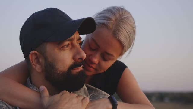 Wife hugging wheelchaired husband Medium close-up of wife hugging wheelchaired soldier husband depression land feature stock videos & royalty-free footage