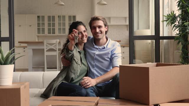 frau zeigt schlüssel sitzen mit mann auf couch in der nähe von boxen - hausschlüssel stock-videos und b-roll-filmmaterial