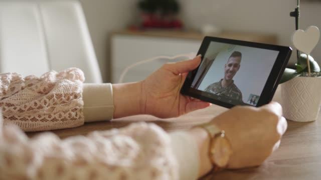 vídeos y material grabado en eventos de stock de esposa hablando con su marido del ejército usando una tableta - casados