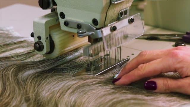 peruk üretim süreci, kadın bir peruk toplar. peruk montajı yakın çekim - peruk stok videoları ve detay görüntü çekimi