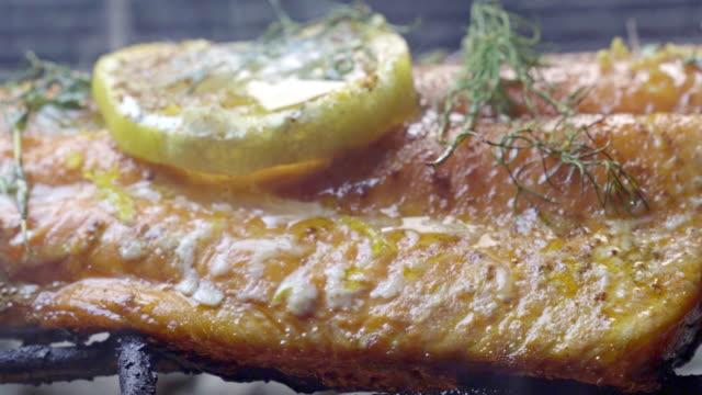 vídeos y material grabado en eventos de stock de salvaje cogido filete de salmón en una parrilla ardiente con rodaja de limón y hierbas - pescado y mariscos