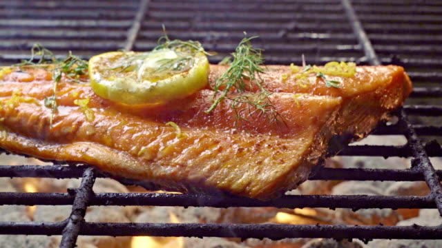 wild caught salmon filet on a fiery grill topped with lemon slice and herbs - ryba filmów i materiałów b-roll