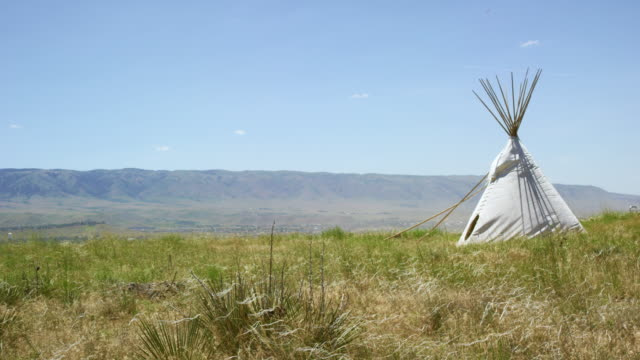 Wild Grasses Blow in the Wind in Front of a Native American Teepee Near Casper, Wyoming with Mountains in the Background under a Clear, Sunny Sky