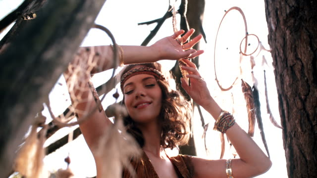 Wild looking girl outdoors in Boho hippie style Boho Girl wearing North American tribal style clothes smiling in nature amongst dead branches and with a dream catcher hanging nearby boho stock videos & royalty-free footage