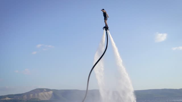 Wild man flying straight up on flyboard Unrecognizable flyboarder connected by long hose riding and balancing on background of blue sky hobbies stock videos & royalty-free footage