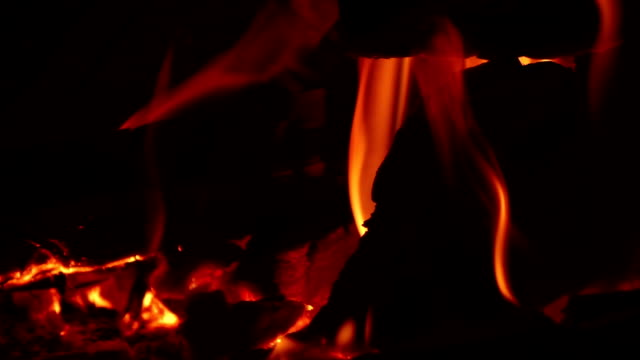 Wild yellow flames raging against black background in slow motion video