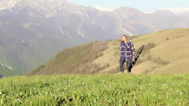 Wildlife nature photographer walking with tripod at mountain landscape video