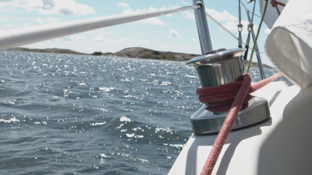 A winch on the railing of the deck of a white sailing boat at sea - slowmotion footage.