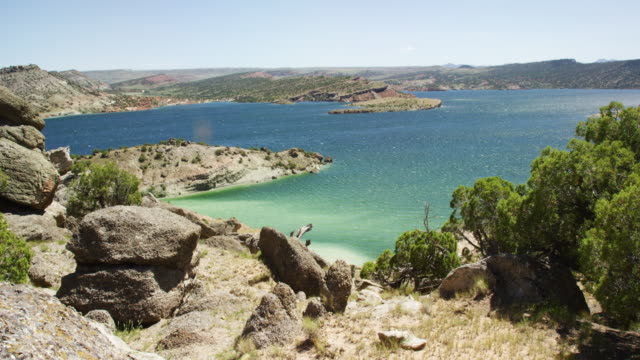 Wind Blows Ripples across Alcova Reservoir Surrounded by Hilly, Rocky Terrain near Casper, Wyoming under a Clear, Sunny Sky