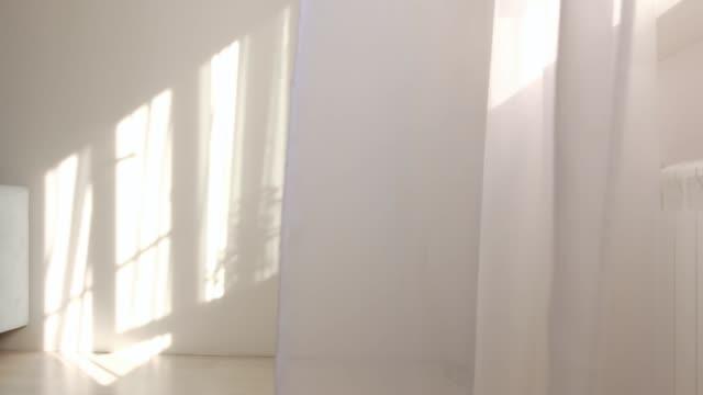 部屋の開いた窓から風が吹く。窓の近くで白いチュールを振る。朝日は部屋を照らす、影の背景オーバーレイ - 壁点の映像素材/bロール