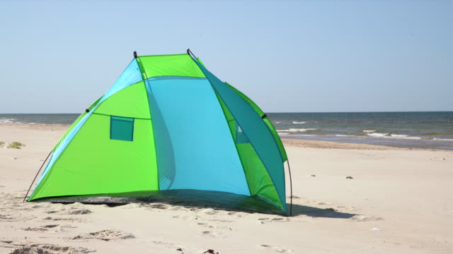Wind breaker tent on a sandy beach by the sea. Nobody. Colorful tent protection from wind and sunburn.