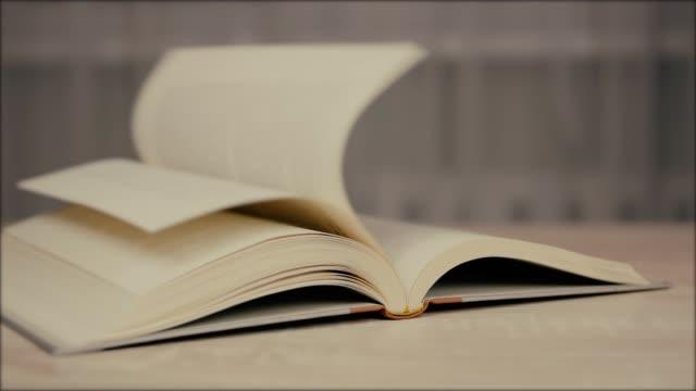 風流覽老書頁。活的書。舊的教育歷史書與下落的紙頁在背面。 - book open 個影片檔及 b 捲影像