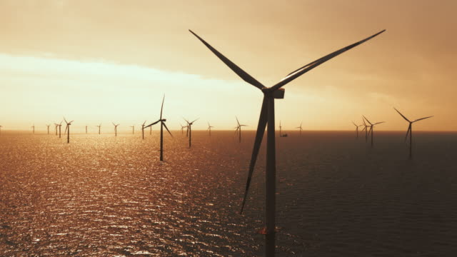 AERIAL Wind farm at sea in sunset Aerial shot of a wind farm at sea in setting sun. Shot in Denmark. denmark stock videos & royalty-free footage