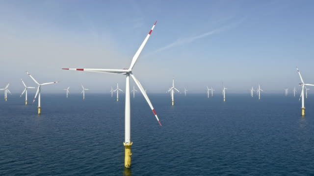 aerial wind farm at sea in sunshine - turbina a vento video stock e b–roll