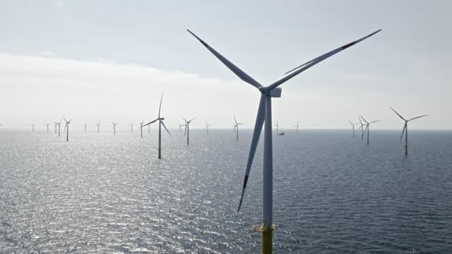 aerial ветропарк в море на солнце - ветряная электростанция стоковые видео и кадры b-roll