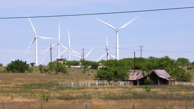 Wind Farm Turbines Turn Over Old Barn in Rural Texas - Medium Shot