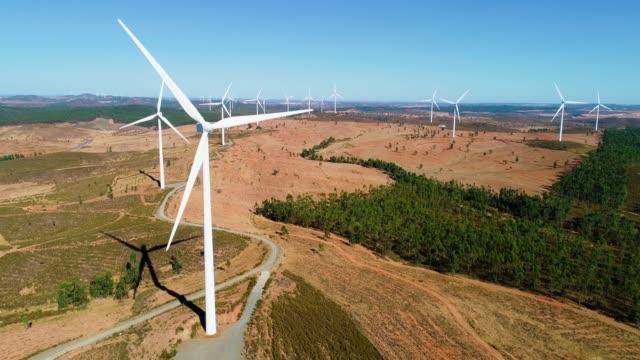 vindpark med vindkraftverk på ett vackert landskap under den blå himlen. förnybar energiproduktion för green environmental world-flygfoto med en drone-miljö & ekologiskt koncept - vindsnurra jordbruksbyggnad bildbanksvideor och videomaterial från bakom kulisserna