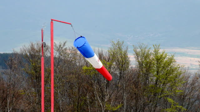 wind sock - red , blue and white pointer indicating strength and direction of the wind against the blue sky - rękaw filmów i materiałów b-roll