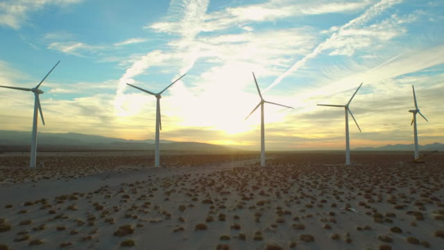 Wind Turbine Aerial v8 Flying low below large wind turbines at sunrise. windmill stock videos & royalty-free footage
