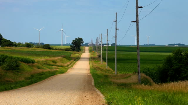 Wind turbine country road Video of a country road with farm crops on either side in the foreground with Wind Turbines spinning in the background country road stock videos & royalty-free footage
