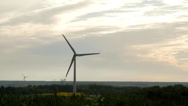 stockvideo's en b-roll-footage met turbine windpark met stralen van licht bij zonsondergang - duurzaam toerisme