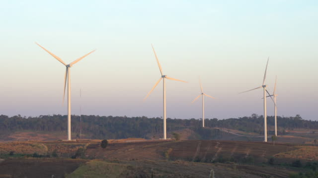 Wind turbine farm with rays of light at sunset. video