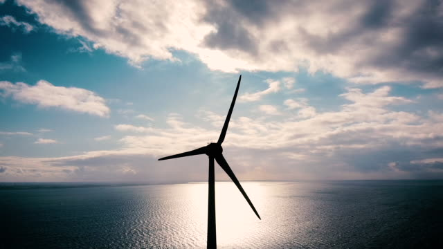 Wind turbine from aerial view. Sustainable development, environment friendly. Windmill silhouette with view over water Wind turbine from aerial view. Sustainable development, environment friendly. Windmill silhouette with view over water. Blue sky, sunset. sustainable living stock videos & royalty-free footage
