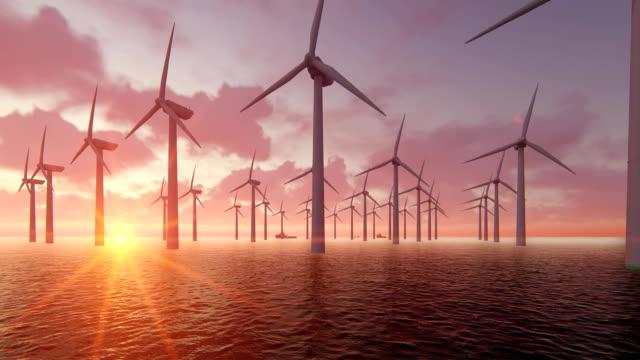 vídeos de stock e filmes b-roll de wind turbine power generators silhouettes at ocean at sunset. - transatlântico