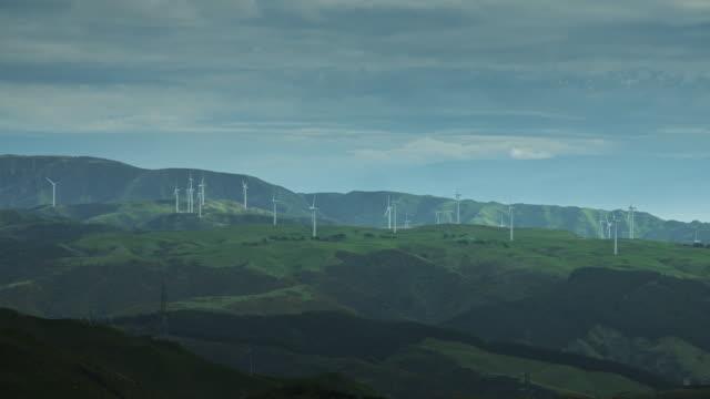 vídeos de stock e filmes b-roll de wind turbines against bay of water - wellington