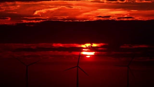 Wind turbines against red sunset
