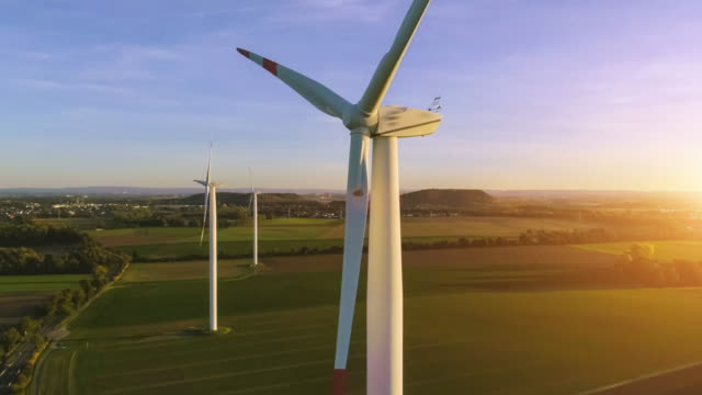 wind turbines and agricultural fields on a summer day - turbina a vento video stock e b–roll