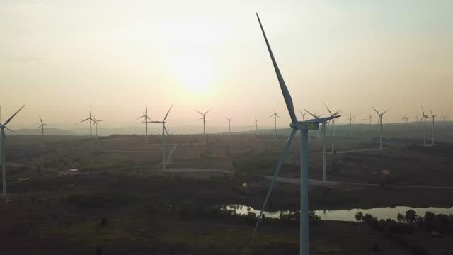 vidéos et rushes de éoliennes au coucher du soleil produisant des énergies renouvelables - science et technologie